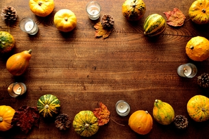 南瓜と枯葉とキャンドルのフレーム 木材背景の写真素材 [FYI01207461]