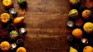 南瓜と枯葉とキャンドルのフレーム 木材背景の写真素材 [FYI01207470]