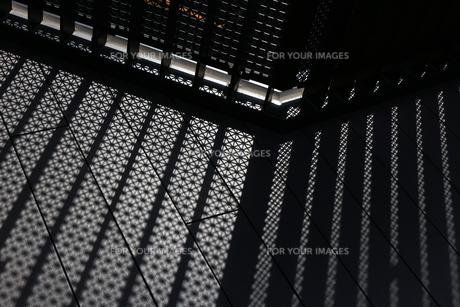 黒色の幾何学的模様のフェンスを通る白い光の写真素材 [FYI01207498]
