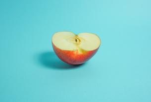 半分に切ったりんご 水色背景の写真素材 [FYI01207861]
