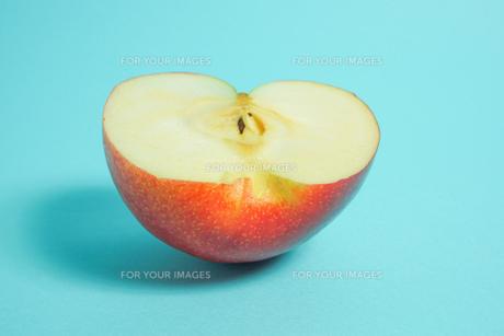 半分に切ったりんご 水色背景の写真素材 [FYI01207862]
