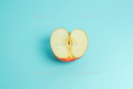 半分に切ったりんご 水色背景の写真素材 [FYI01207863]