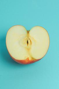 半分に切ったりんご 水色背景の写真素材 [FYI01207864]