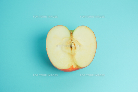 半分に切ったりんご 水色背景の写真素材 [FYI01207865]