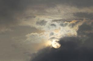 曇り空の隙間から見える満月に似た太陽の写真素材 [FYI01209860]