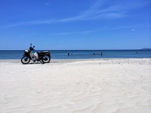 白浜とバイク(カブ)の写真素材 [FYI01210138]
