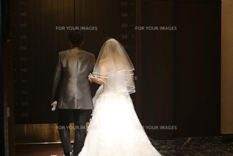 結婚式の花嫁と新郎の背中 扉から出ていくの写真素材 [FYI01210194]