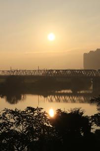 川に架かる鉄橋の後ろに太陽がある景色の写真素材 [FYI01210299]