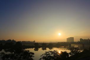 川に架かる鉄橋の後ろに太陽がある景色の写真素材 [FYI01210300]