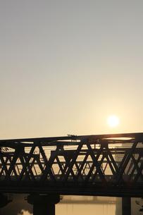 川に架かる鉄橋の後ろに太陽がある景色の写真素材 [FYI01210301]