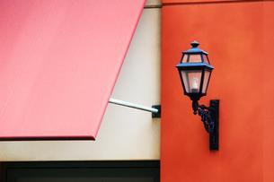 赤い壁に取り付けられた黒いアンティーク調の外灯の写真素材 [FYI01212186]