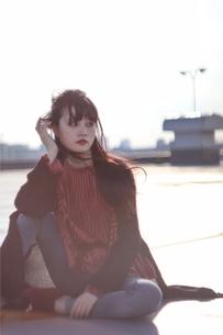 屋上の夕日、座り込む女性ポートーレートの写真素材 [FYI01215194]