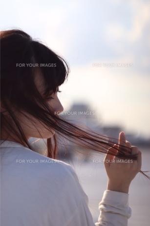 太陽で透ける髪、夕日に照らされる女性の写真素材 [FYI01215209]