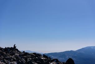 溶岩石の山頂から他の山脈を見る登山者の写真素材 [FYI01216060]