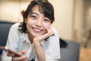 ソファに寝転がり笑顔携帯を持つOL女性の写真素材 [FYI01216312]