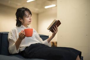 ソファに座りカップを片手に本を読む女性の写真素材 [FYI01216317]