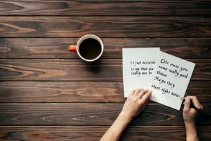 木目のテーブルの上にコーヒーカップを置いて便箋に文字を書いている所の写真素材 [FYI01216412]