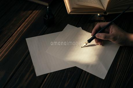 ペンを持つ手と便箋と木の机と本。の写真素材 [FYI01216428]