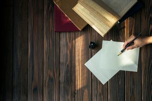 便箋とペンを持つ手と本と木目のテーブルの写真素材 [FYI01216430]