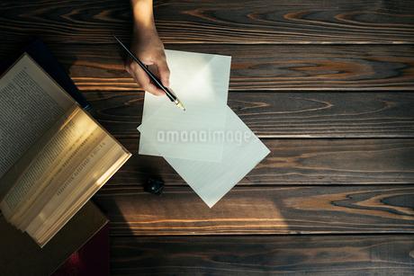 ペンを持つ手と本と木目のテーブル。差し込む光。の写真素材 [FYI01216431]