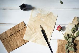 紙の上に置いたペンと、散りばめた封筒と紙と花の写真素材 [FYI01216573]