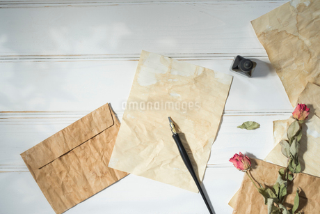 紙の上に置いたペンと、散りばめた封筒と紙と花の写真素材 [FYI01216575]