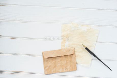 俯瞰構図の白木の背景とペンと紙と封筒。の写真素材 [FYI01216581]
