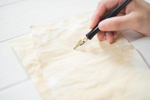 紙の上でペンを持つ手の写真素材 [FYI01216584]