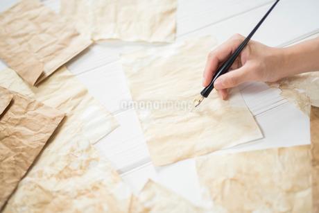 紙の上でペンを持つ手とアンティークな紙と封筒の写真素材 [FYI01216585]