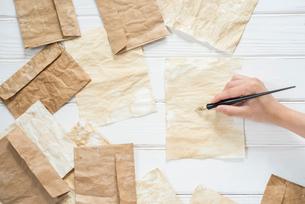 横構図の散りばめたアンティークな紙と封筒とペンを持つ手の写真素材 [FYI01216586]