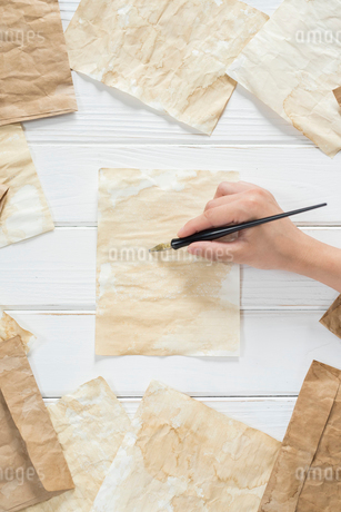 散りばめたアンティークな紙と封筒とペンを持つ手の写真素材 [FYI01216587]