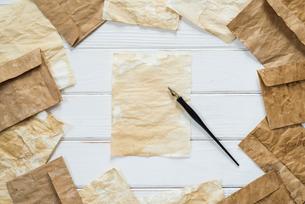 散りばめたアンティークな紙と封筒とペンの写真素材 [FYI01216589]