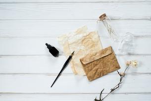 ペンとインクとアンティークな紙と封筒と小瓶と花の写真素材 [FYI01216591]