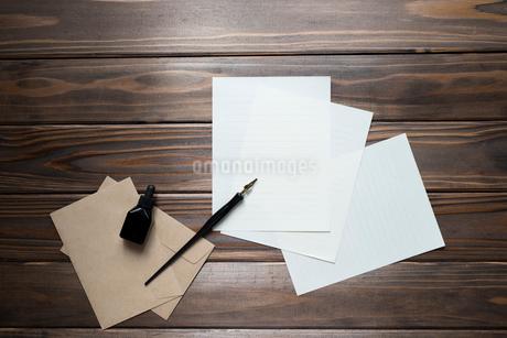 机の上に置いたペンと紙と封筒とインクの写真素材 [FYI01216593]