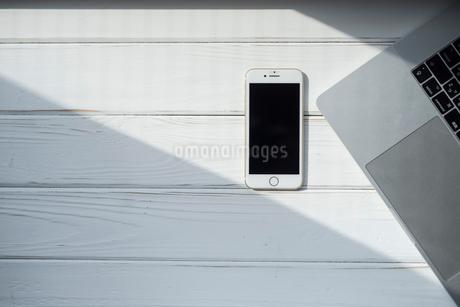 携帯とPCに差し込む光の写真素材 [FYI01216606]
