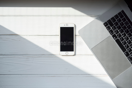 白い木目の床に置かれた携帯とPCの写真素材 [FYI01216608]