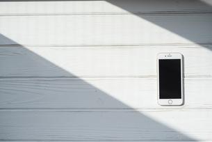 白い木目の床に置かれたiPhoneの写真素材 [FYI01216609]