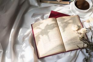 アンティークな本とドライフラワーとコーヒーカップに差し込む光の写真素材 [FYI01216611]