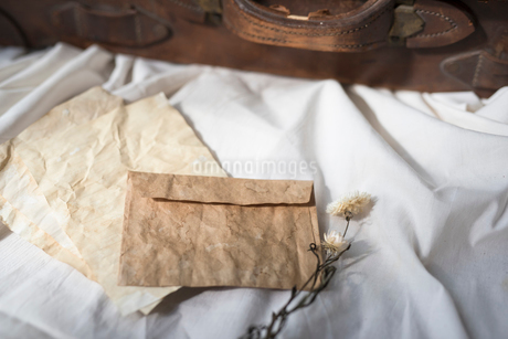 白布の上に置いた封筒と紙と旅行鞄の写真素材 [FYI01216616]