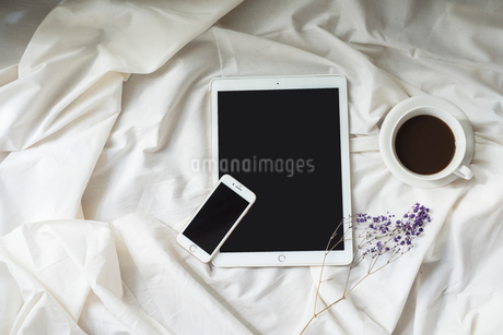 iPadとiPhoneとコーヒーカップと花の写真素材 [FYI01216619]