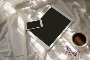 白い布の上に置いた、iPadとiPhoneとコーヒーカップと花の写真素材 [FYI01216620]