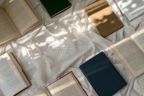白い布の上へ斜めに並べた本に差し込む光の写真素材 [FYI01216628]