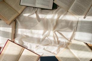 白い布の上に散りばめた本に差し込む光の写真素材 [FYI01216630]