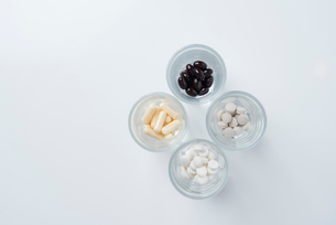 俯瞰で見たガラスのコップの中に薬が入っている様子の写真素材 [FYI01216637]