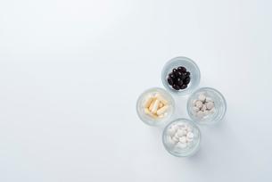 4つのガラスのコップの中に薬が入っているの写真素材 [FYI01216640]