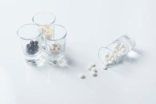 薬の入った4つのガラスコップと白背景の写真素材 [FYI01216649]