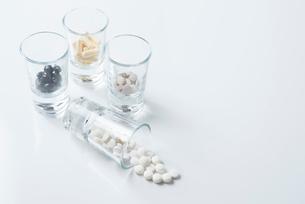 薬の入ったガラスのコップと白背景の写真素材 [FYI01216652]