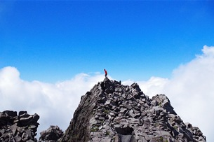 岩山の頂上付近に登山道が一人立っていますの写真素材 [FYI01217101]