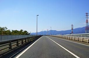 遠くに丹沢山地と富士山が見える直線道路の写真素材 [FYI01219707]