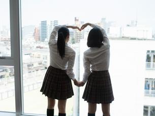 窓の外に向かってポーズをする2人の女子高校生の写真素材 [FYI01220695]